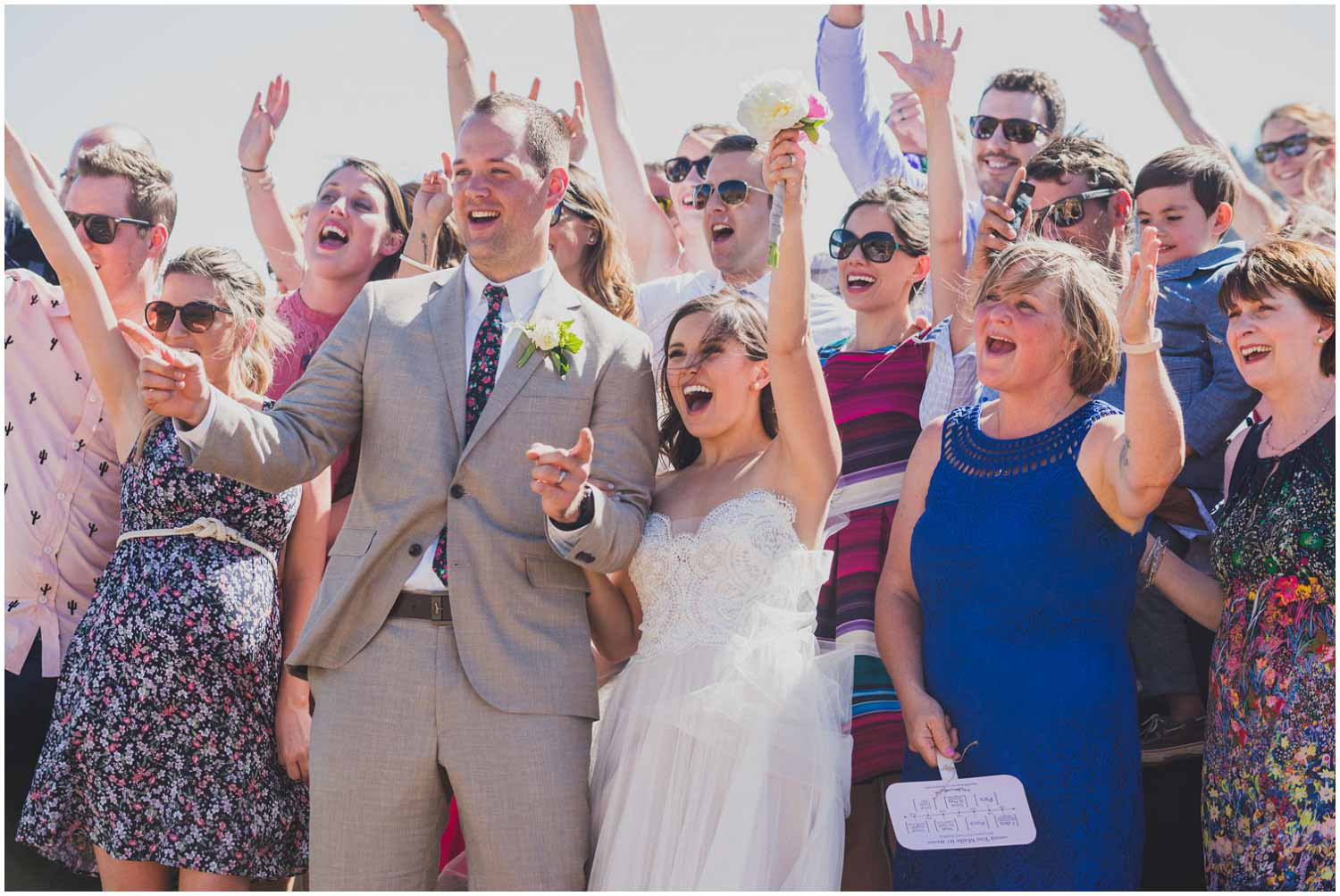 bride and groom cheering with family after wedding ceremony