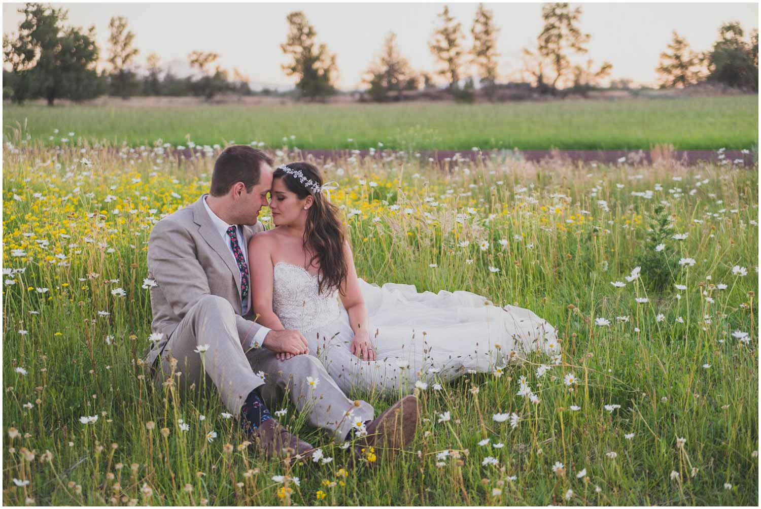 bride and groom snuggling for golden hour portraits in central oregon wild flowers