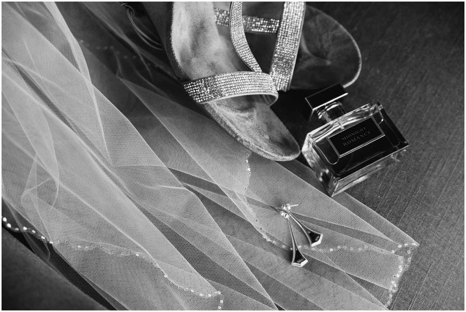black and white of bride's details earrings, veil, shoes, and perfume