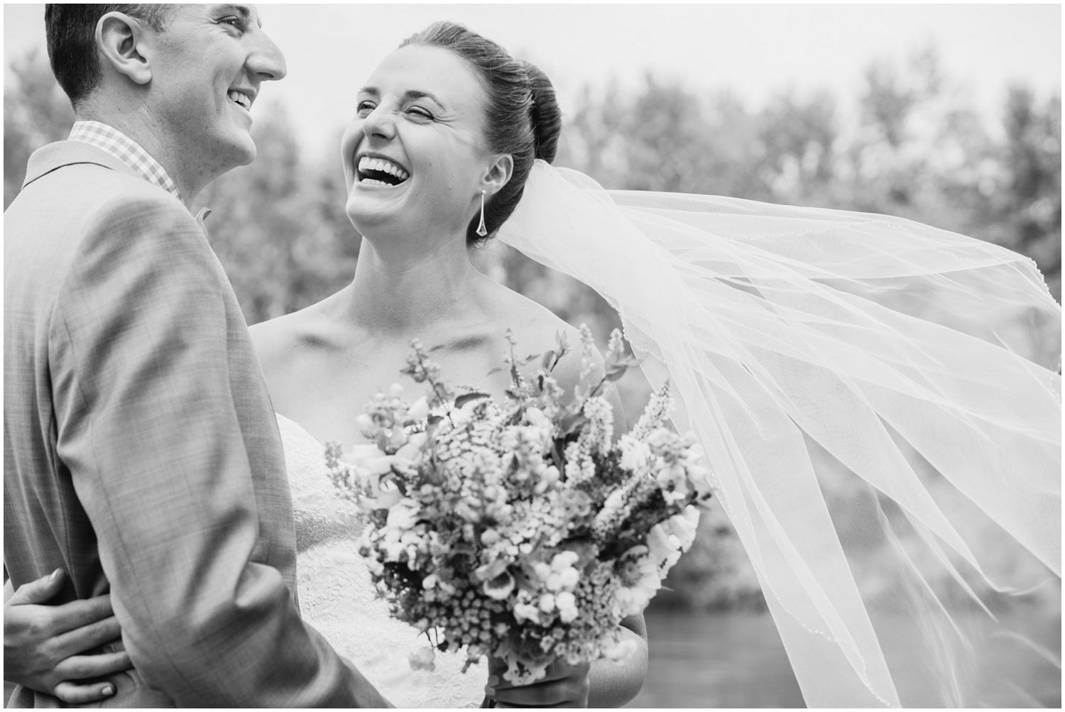 bride has big smile and laugh during portraits with groom