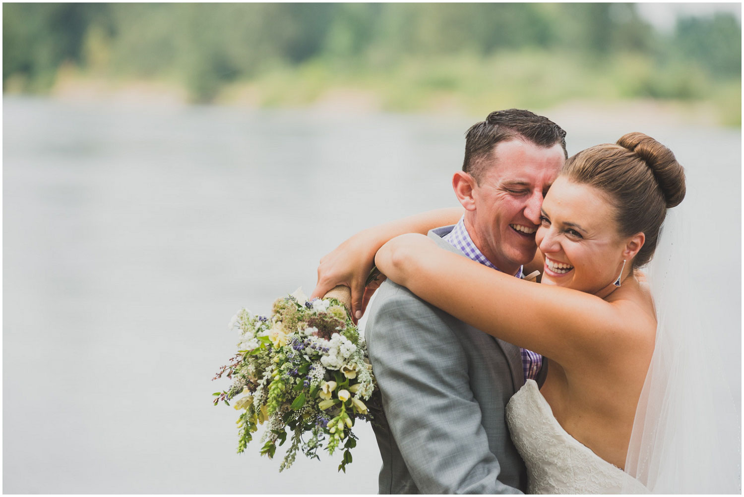 bride and groom laughing and hugging next to the willamette river
