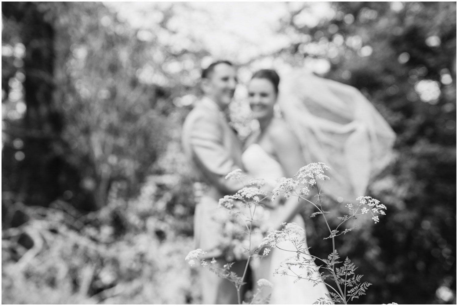 black and white portrait of bride and groom bokehed in background