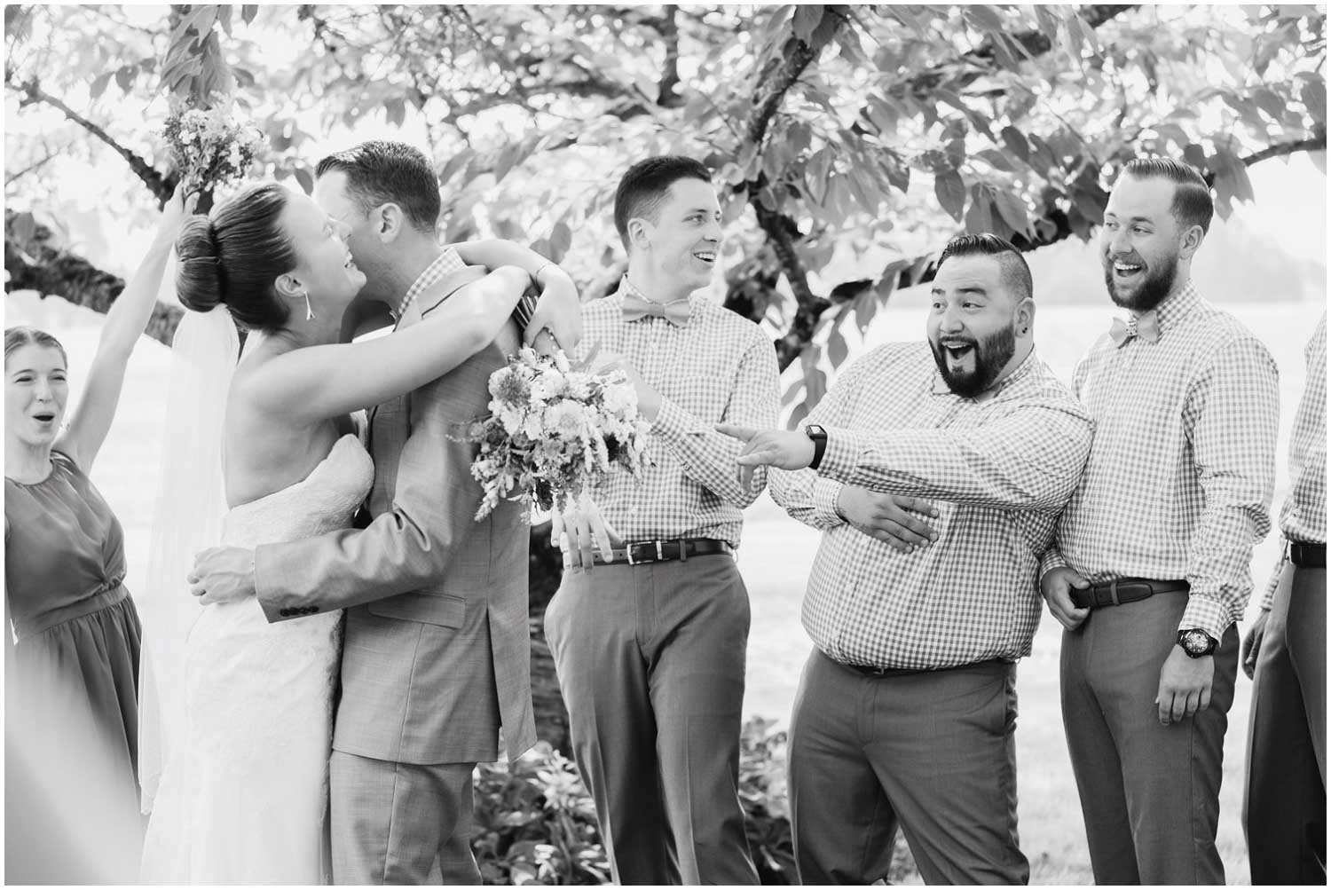 bridesmaids and groomsmen laugh cheer and clap as bride and groom kiss