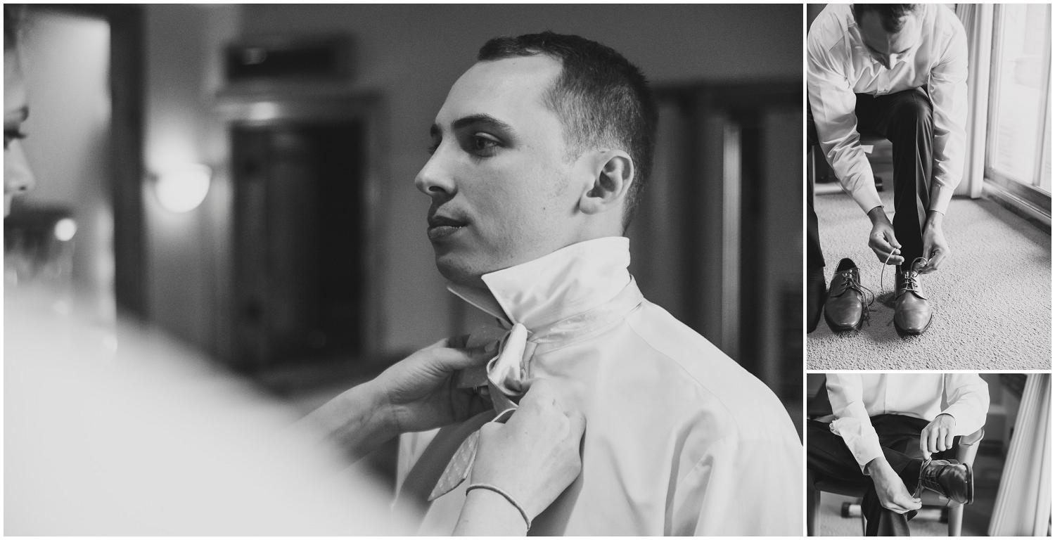 black and white portraits of groom getting dress on wedding day with help from groomsmen