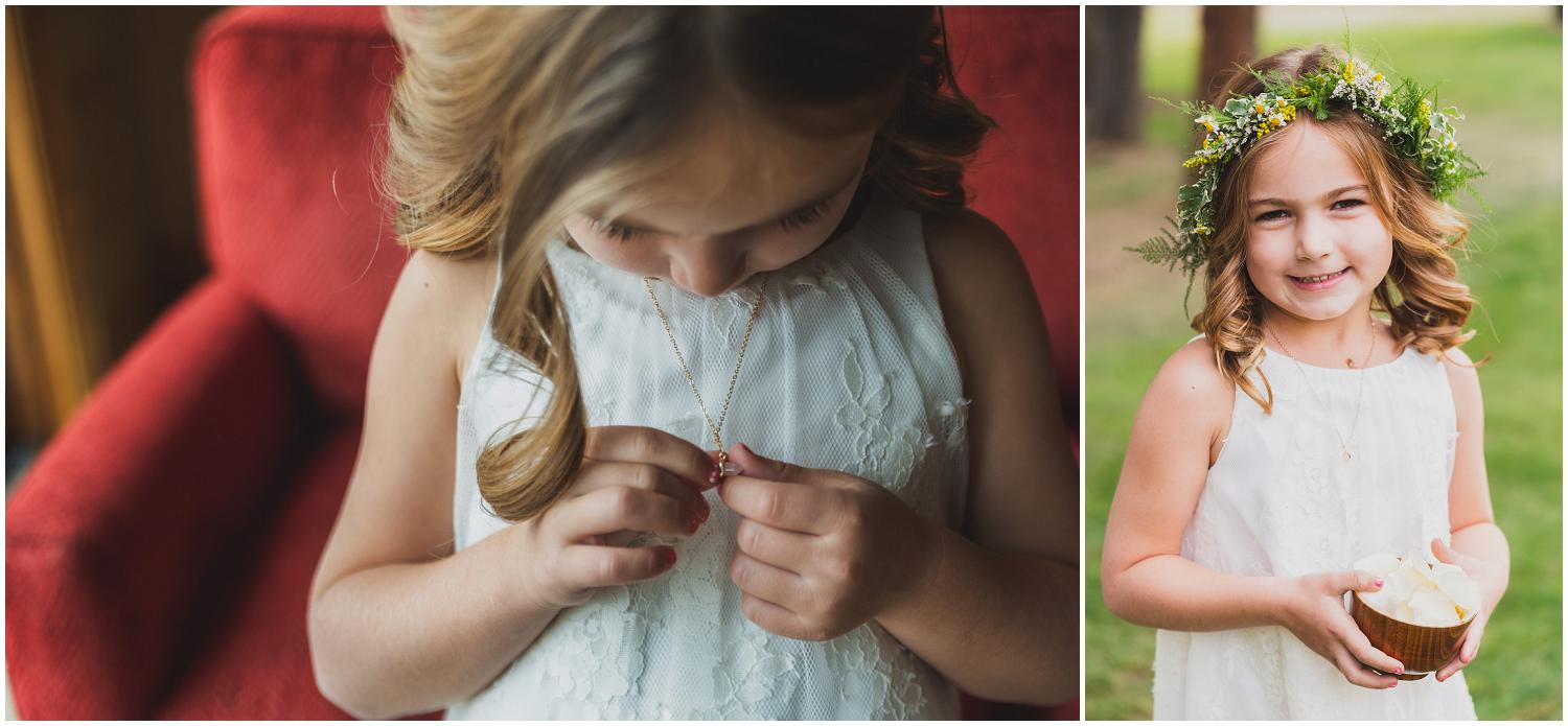 adorable flower girls look at their necklace gifts from bride and groom