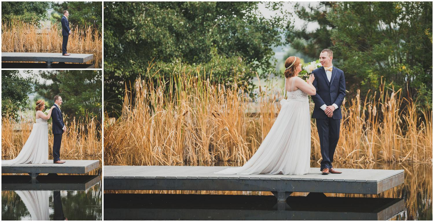 bride and groom first look on a dock with tall reeds behind them