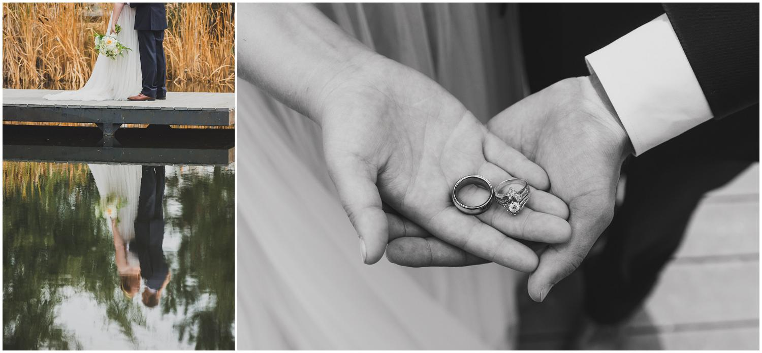 bride and groom reflection in water off dock and holding their wedding rings in their hands together