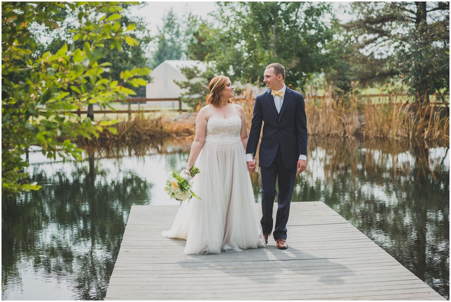 bride and groom walking down pond dock while smiling at each other
