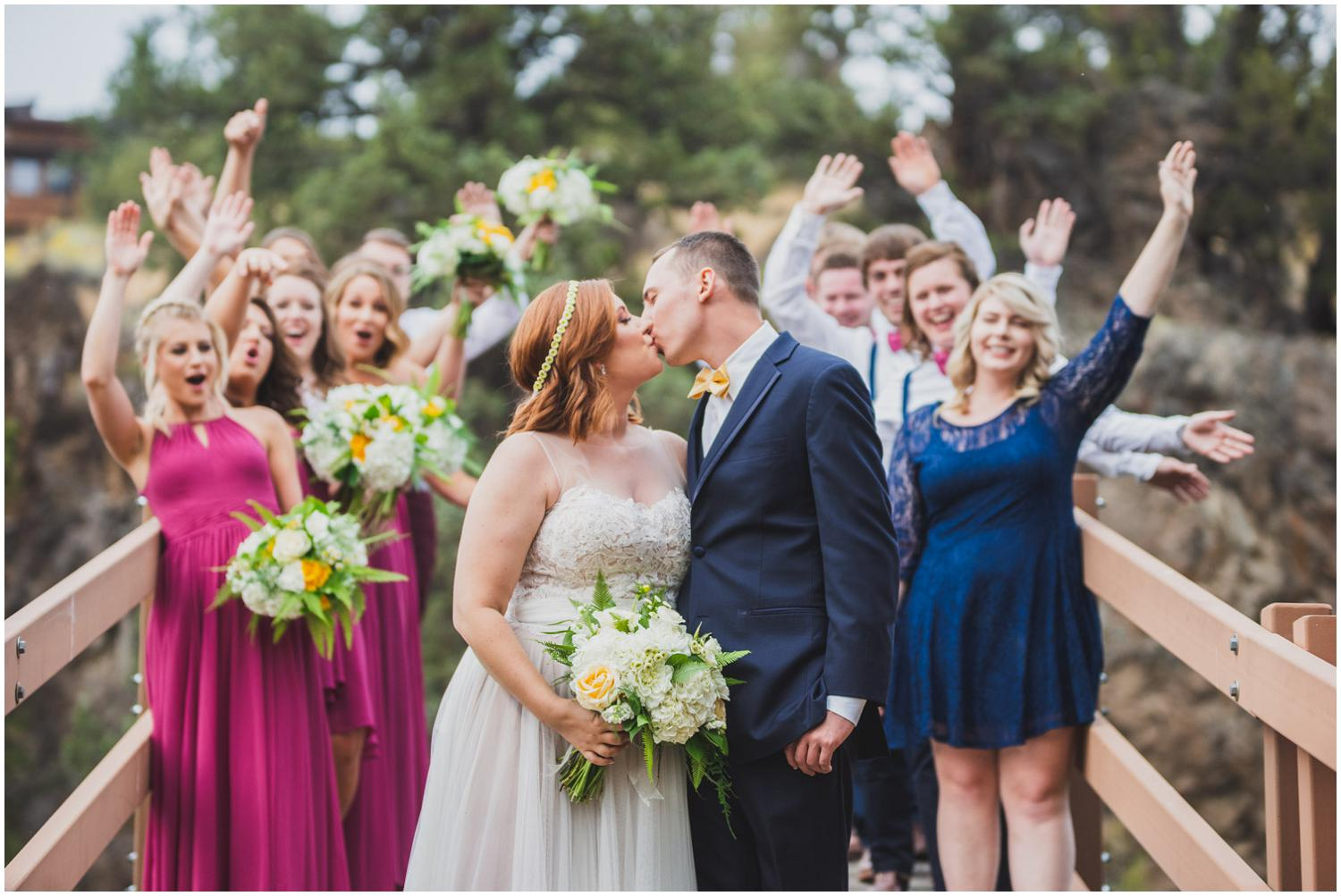 bride and groom kissing on bridge with wedding party cheering behind them