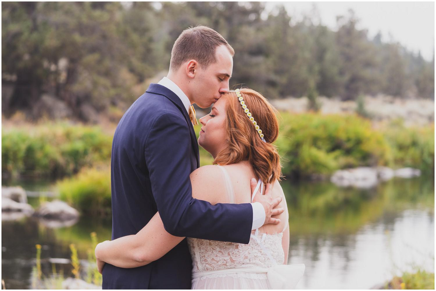 groom tenderly kisses bride's forehead while they look over the river