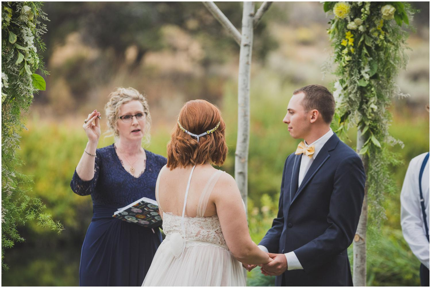 officiant holding up wedding rings while describing meaning and importance