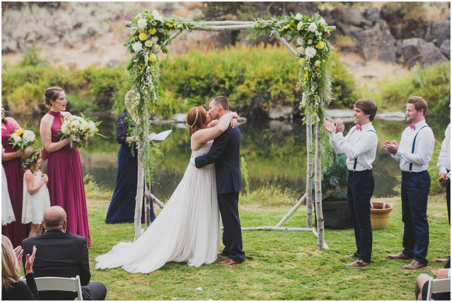 Yay! Bride and groom seal their wedding ceremony with a kiss