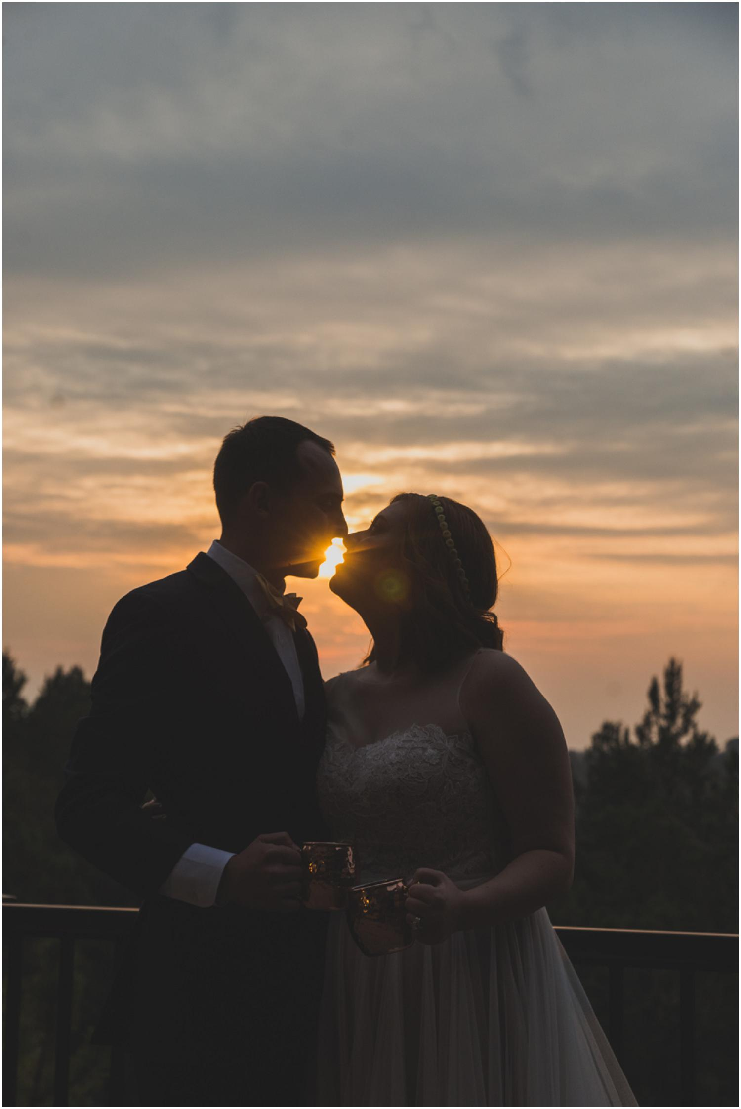 silhouette of bride and groom enjoying a sunset kiss