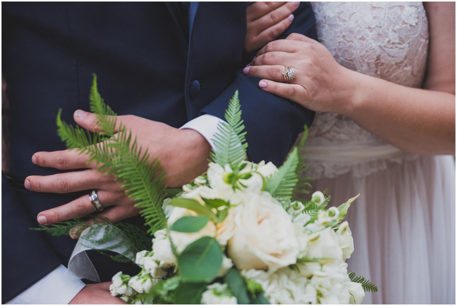 bride snuggling on groom's arm while he holds her flowers