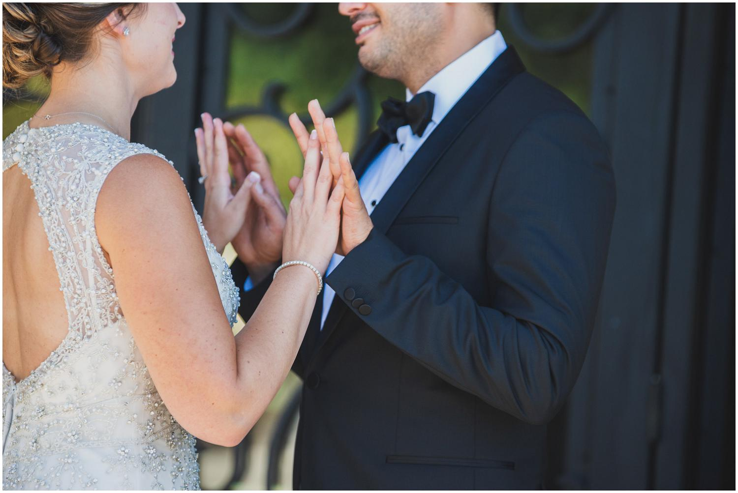 bride and groom gently touch hands after first look
