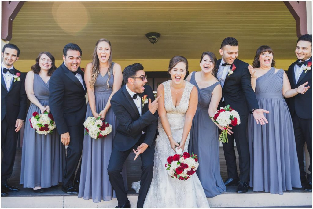 bride and groom laughing with their wedding party on vineyard deck