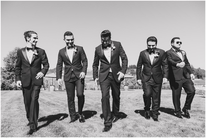 groom and groomsmen walking across lawn like complete badasses