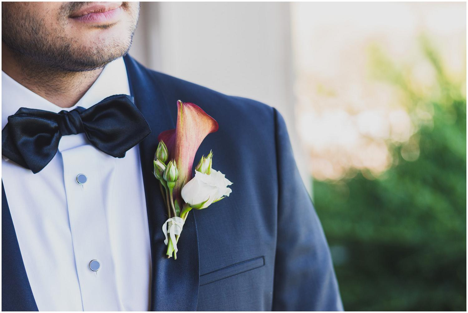 classic groom in black tux with rose and lilly boutonniere