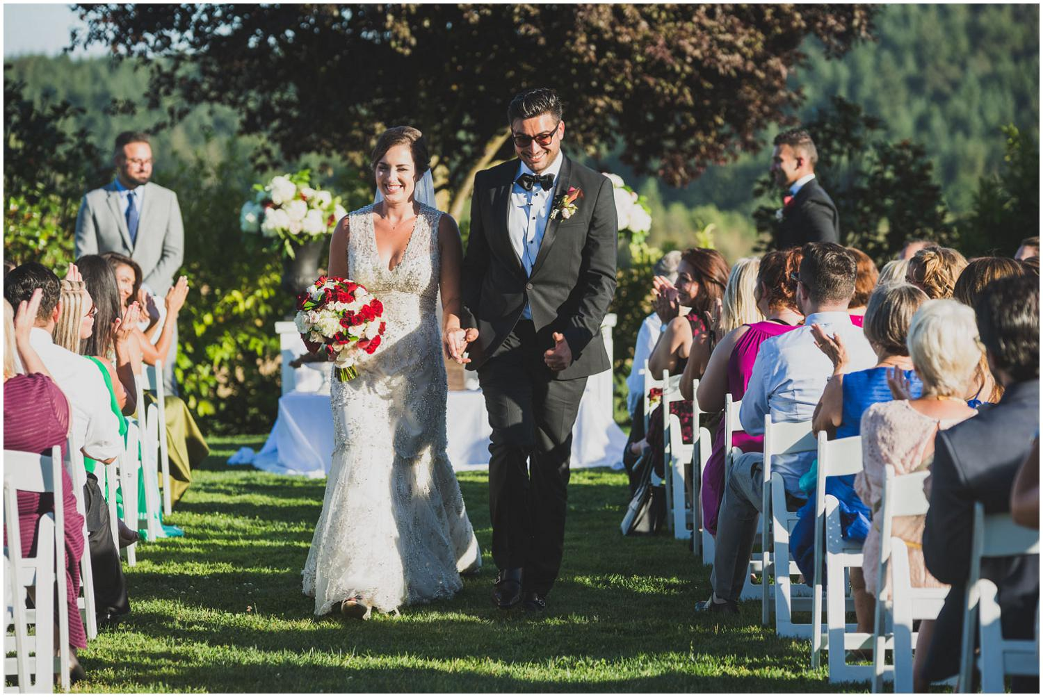 yaaaay! newlyweds walk back down the aisle to applause from friends and family