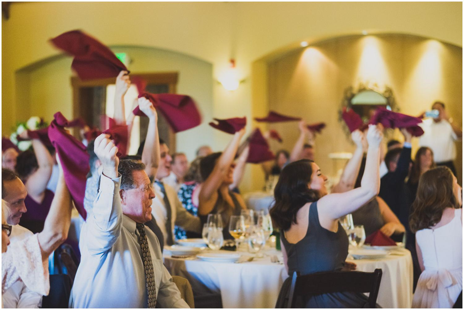friends and family celebrate bride and groom by spinning their colorful napkins overhead