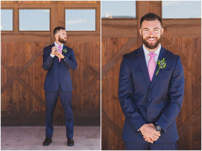 daper groom in blue suit and pink tie in front of barn doors