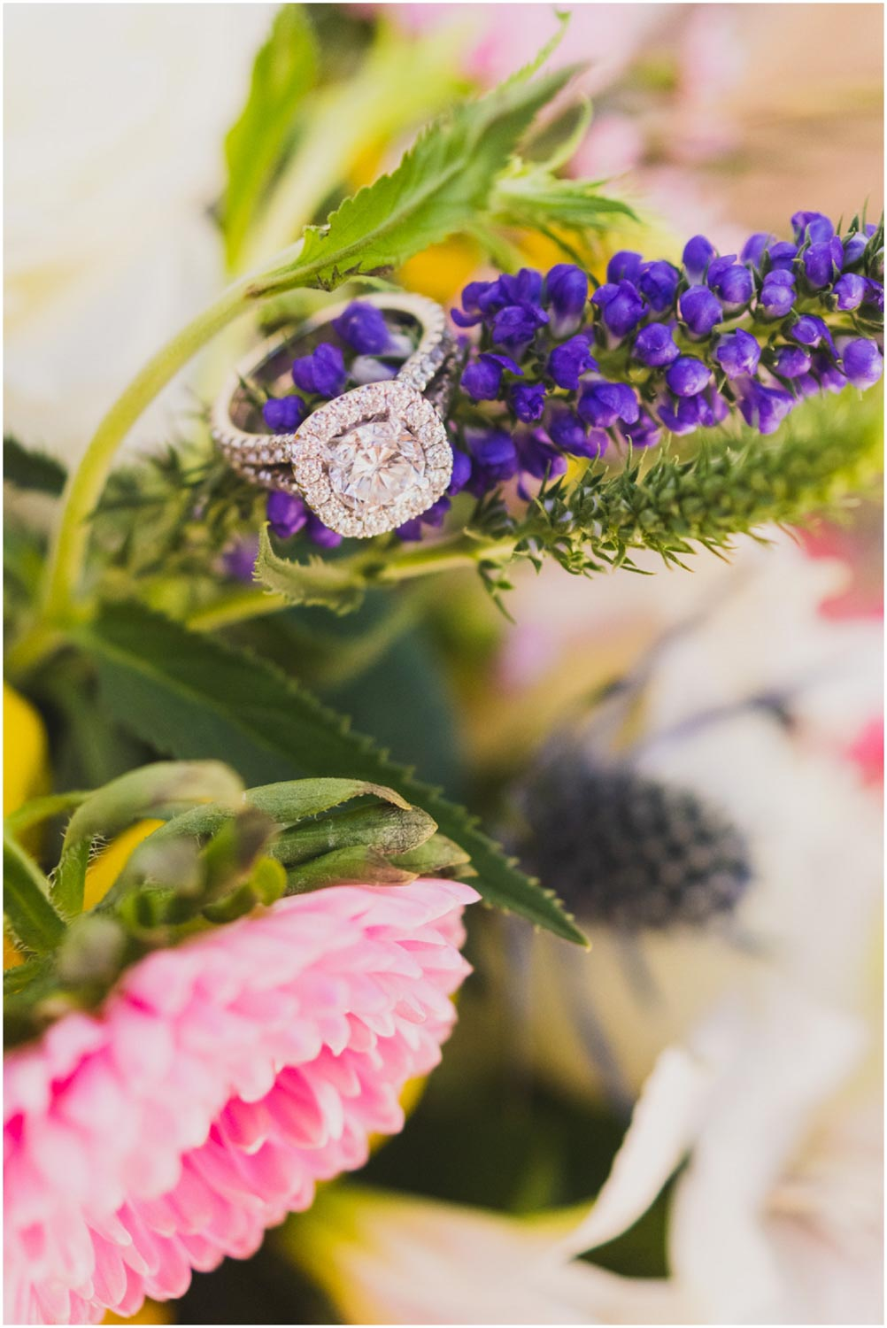 detail photograph of halo engagement ring sitting on bouquet of wildflowers