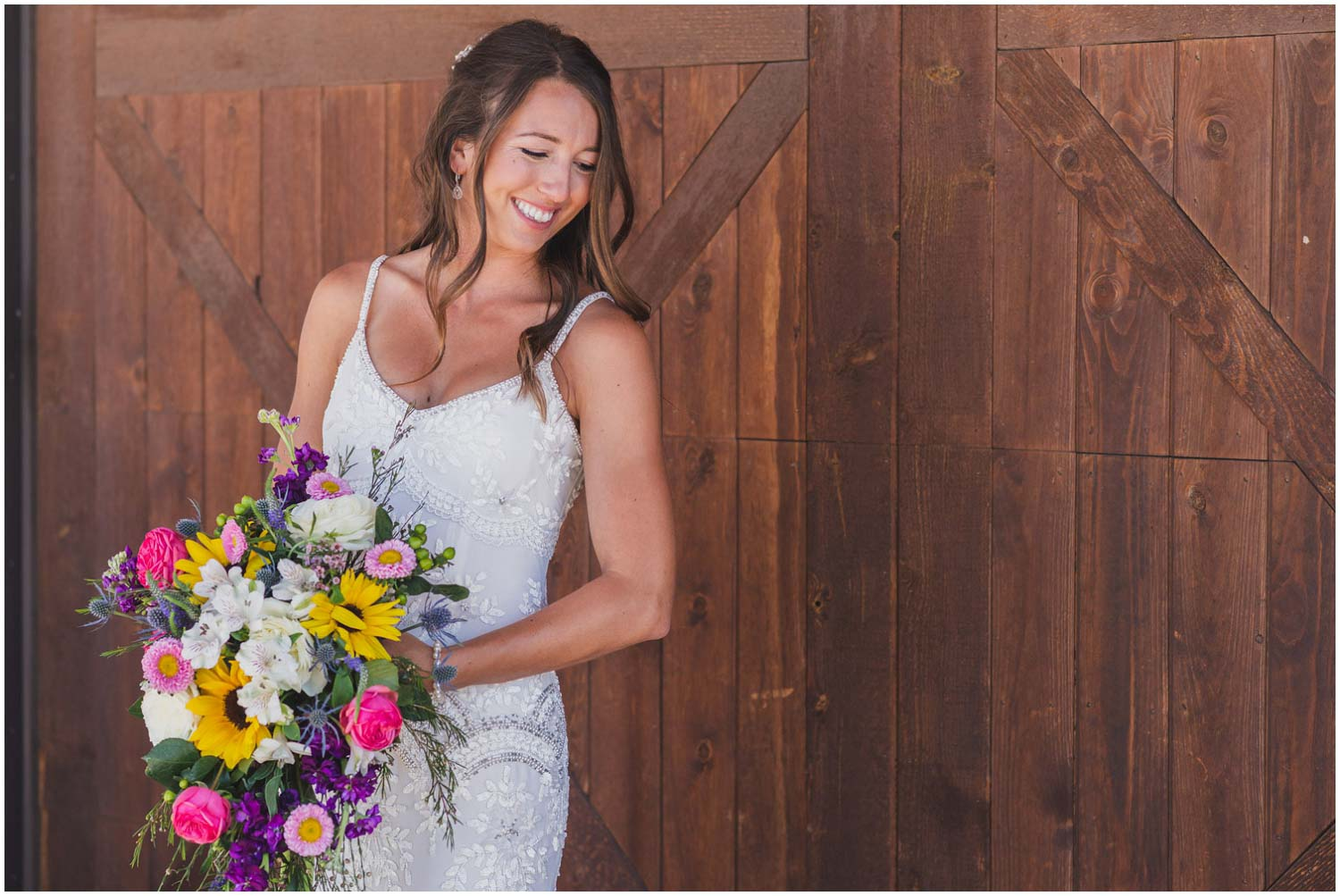 sunkissed bride in front of barn doors in beaded art deco pattern dress with large wildflower bouquet