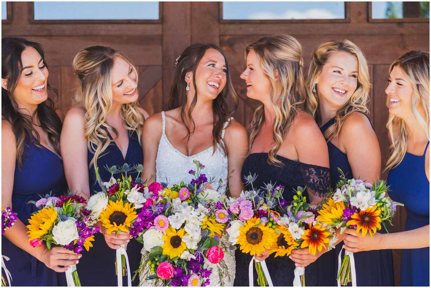 happy bride with her bridesmaids laughing while holding bouquets