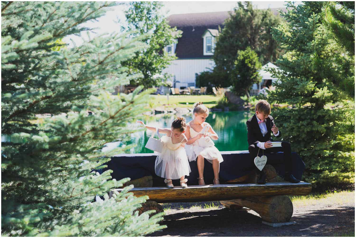 flower girls and ring bearer waiting by the pond for the ceremony to begin