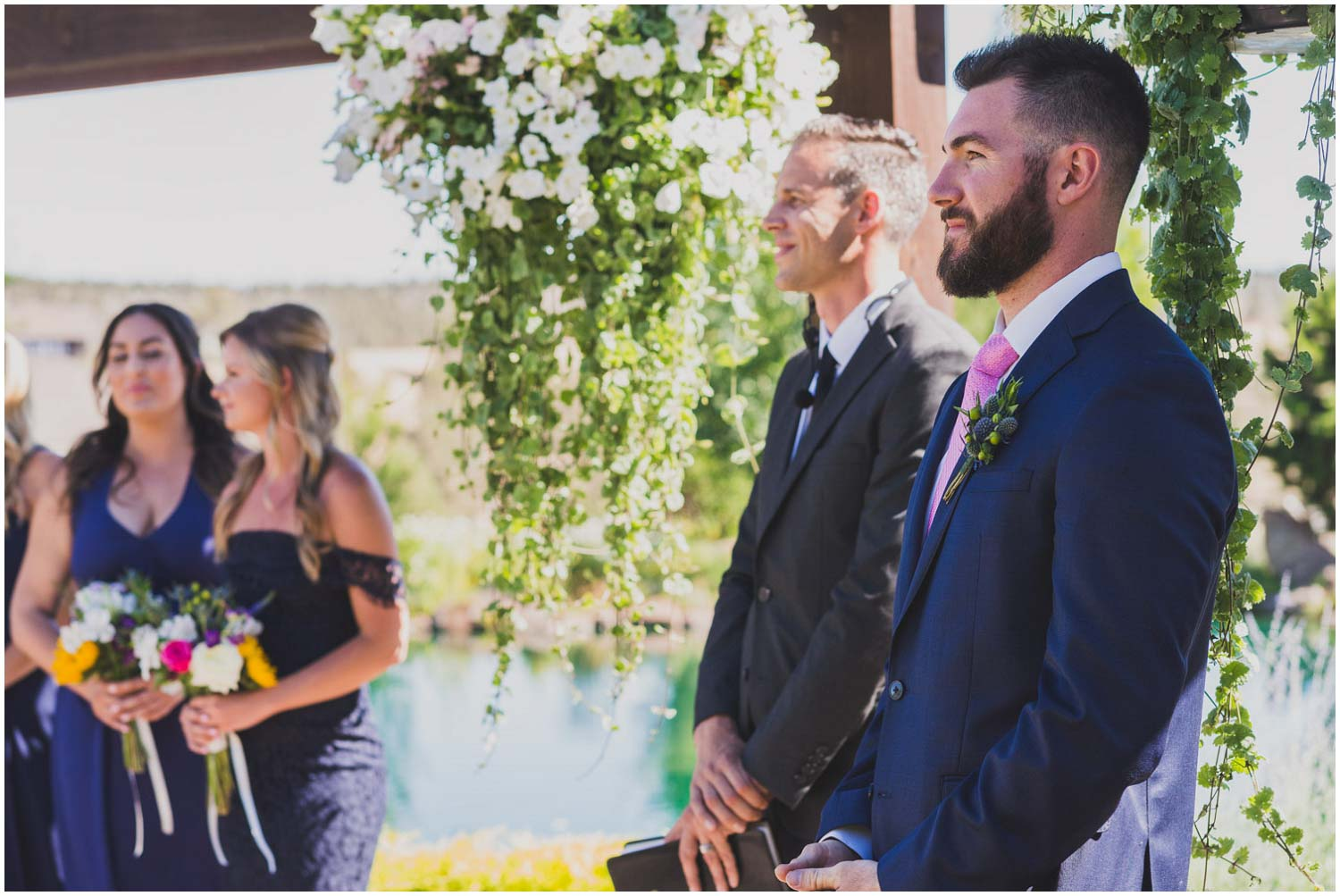 groom with wedding party watches his bride walk down the aisle at faith hope and charity vineyard