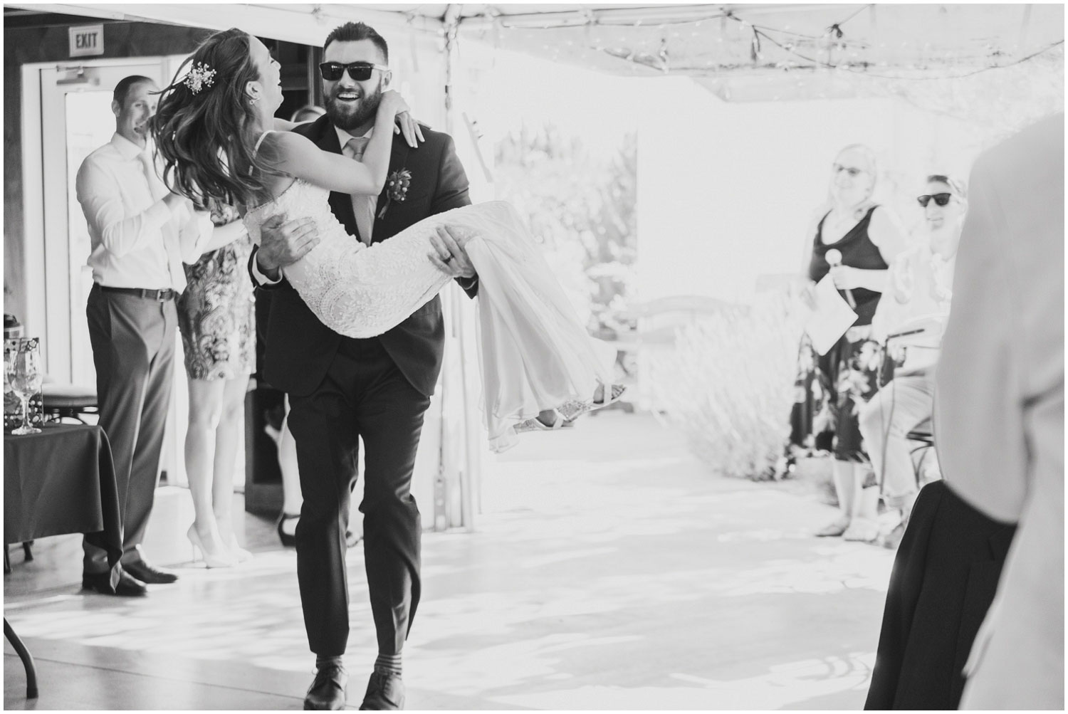 groom carrying bride into reception for wedding toasts and dancing