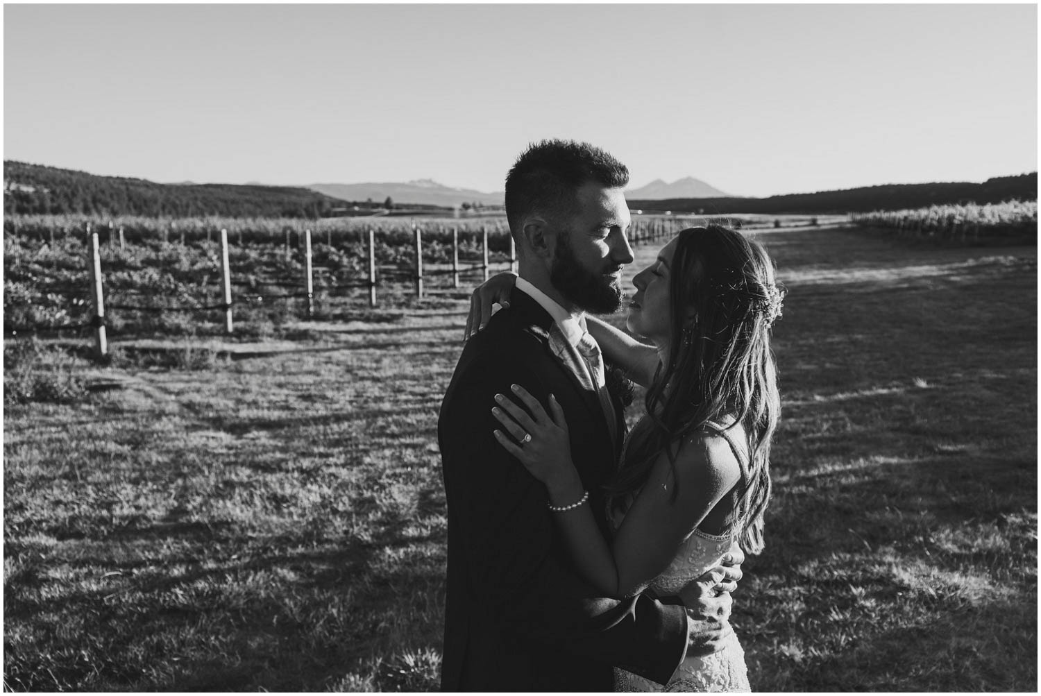 newly wed bride and groom in front of vineyard and mountain view at faith hope and charity madras oregon
