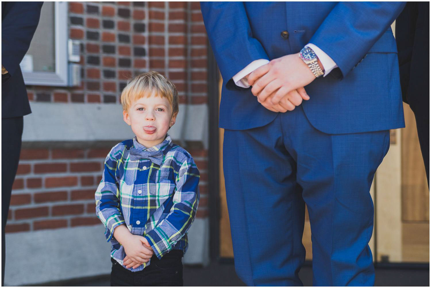 little boy sticking out his tongue during wedding portraits with groom
