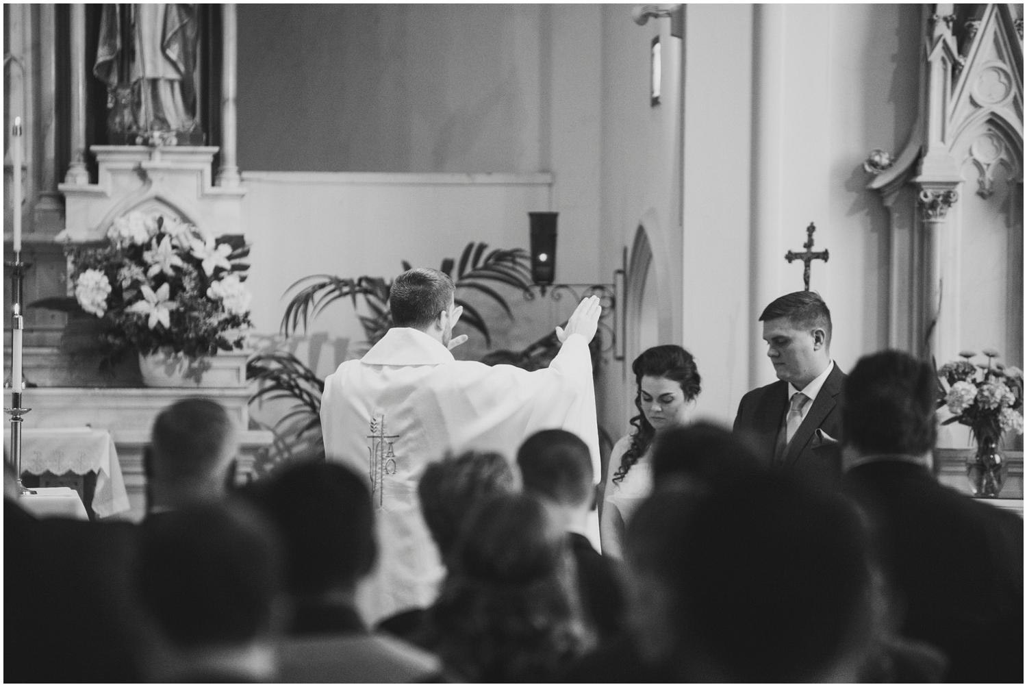priest blessing and praying over bride and groom during catholic wedding ceremony