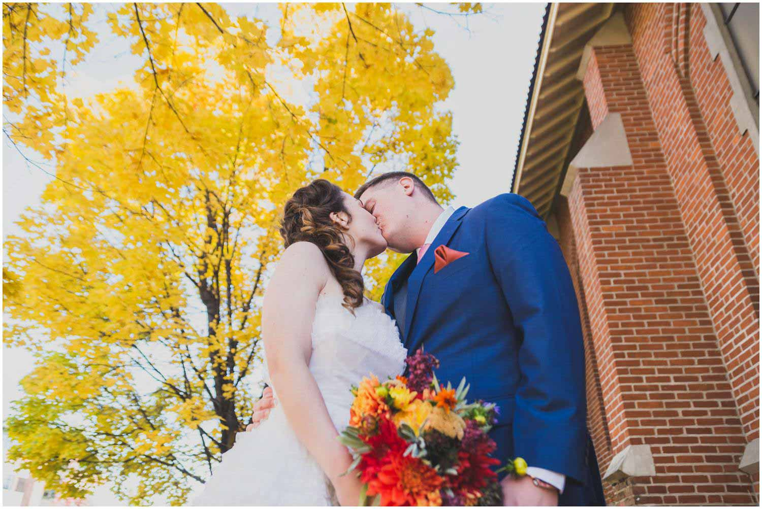 bride and groom kiss under colorful fall leaves outside the historic catholic church downtown bend