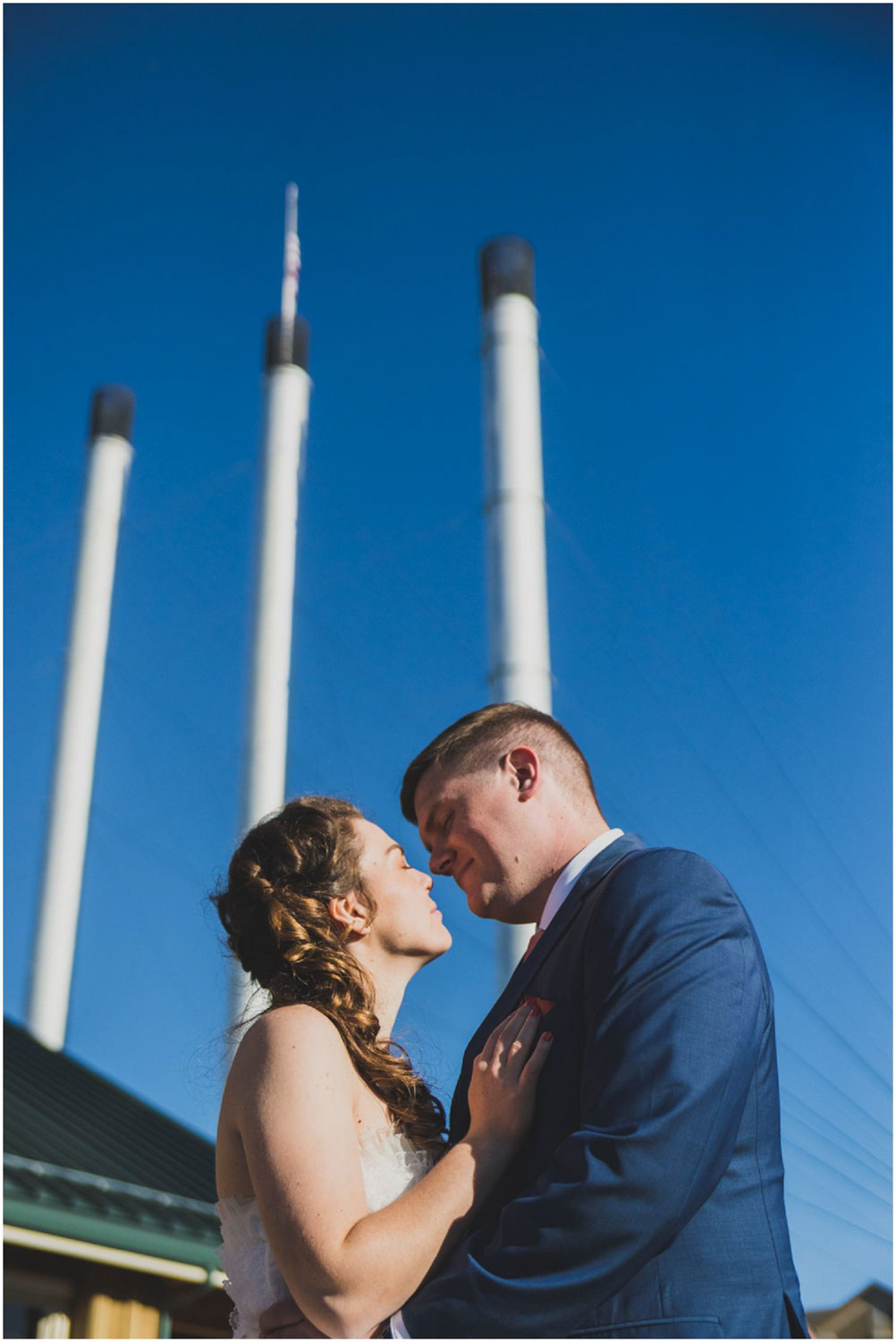 newly wed couple kiss in front of iconic old mill district smoke stacks in bend oregon