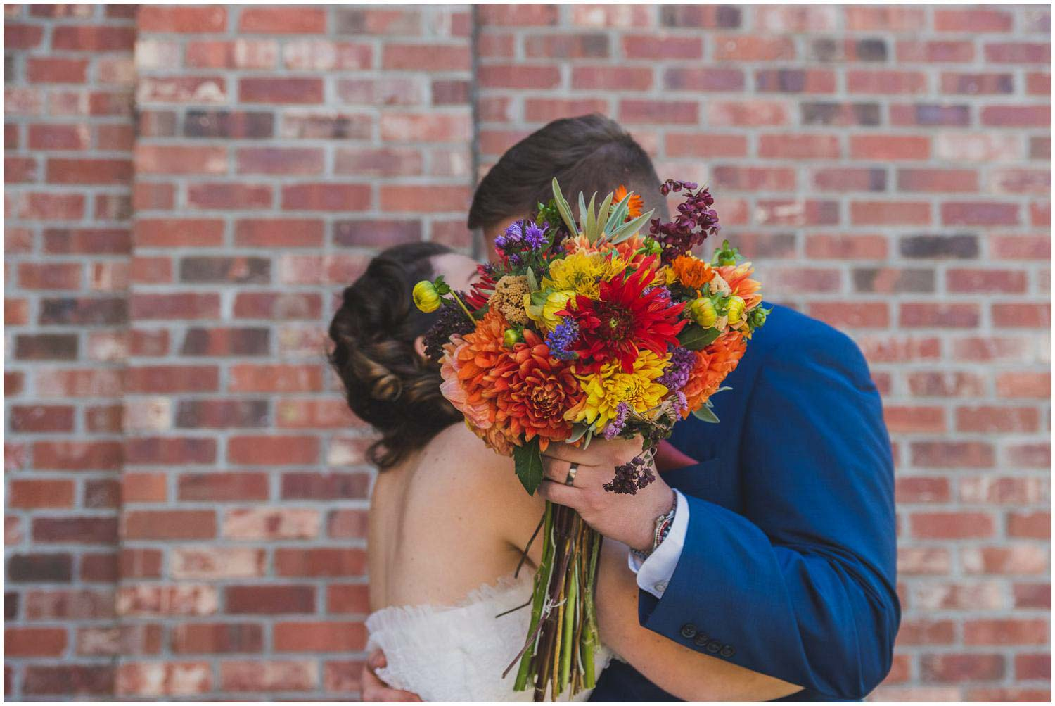 groom blocks the camera's view during kiss with bride's bouquet