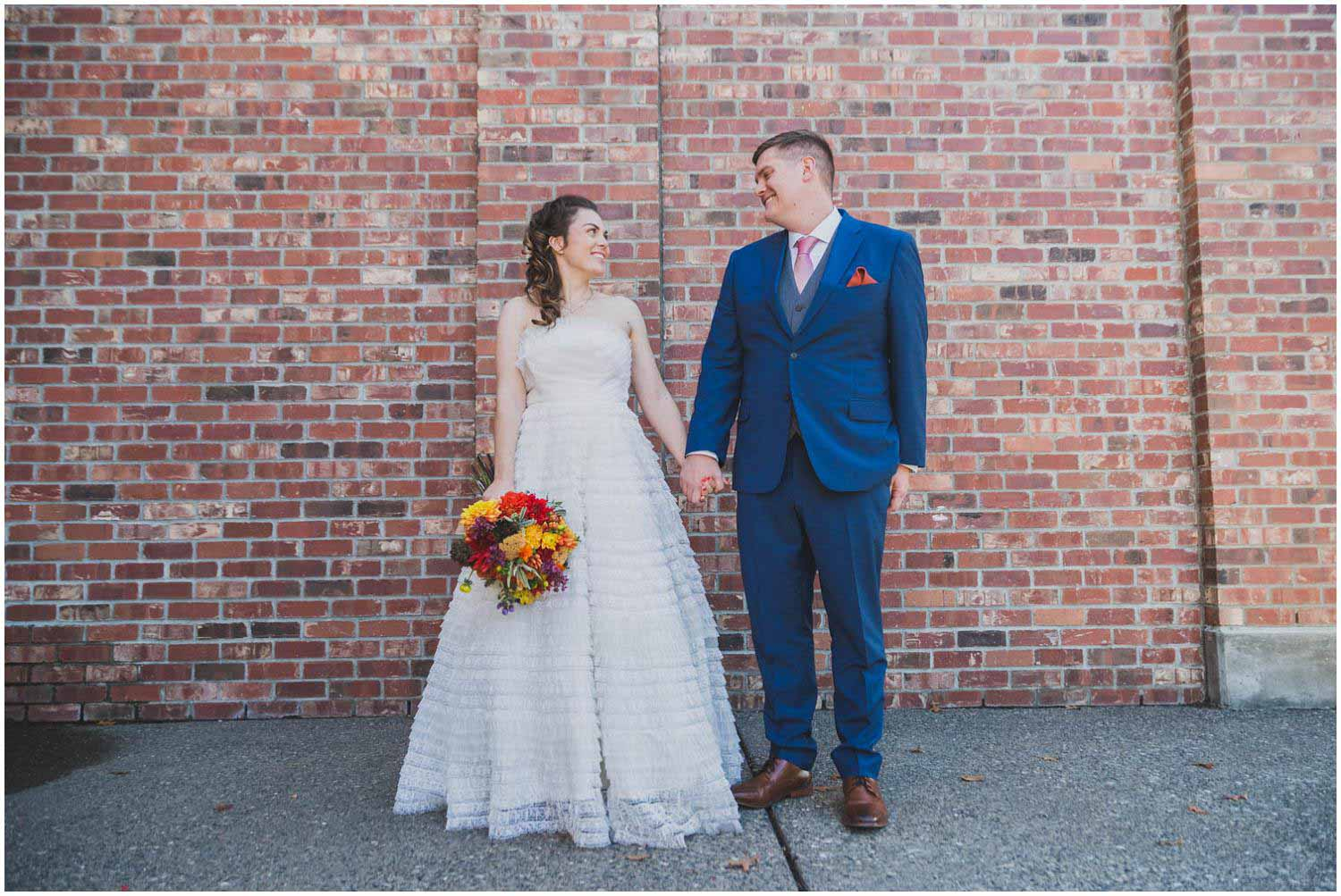 Newly wed couple at Deschutes Brewery in blue suit and heirloom dress