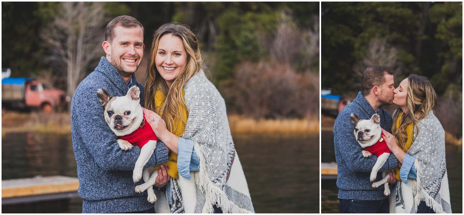 newly engaged couple cuddling with their frenchie dog at the lake