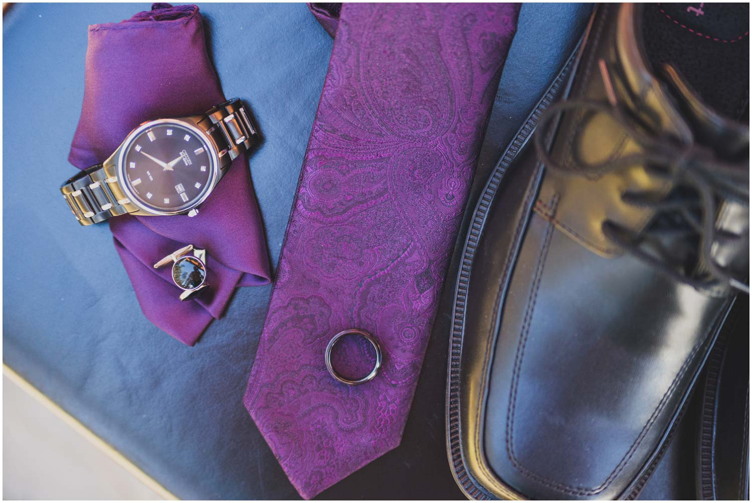 bride's details including purple tie and pocket square, watch and black wedding ring