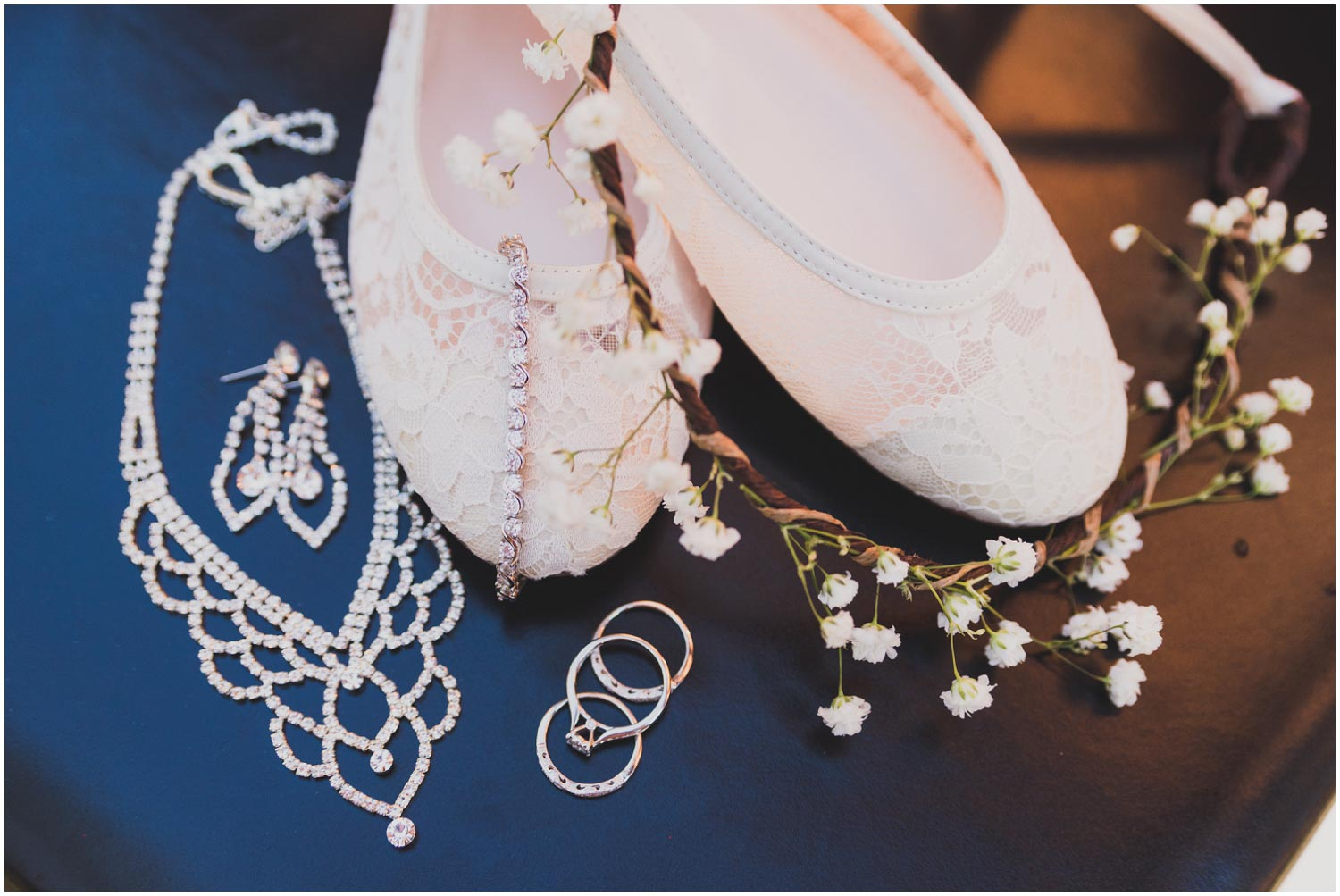 bride's details including rhinestone earrings and necklace, lace shoes, babies breath flower crown and wedding rings