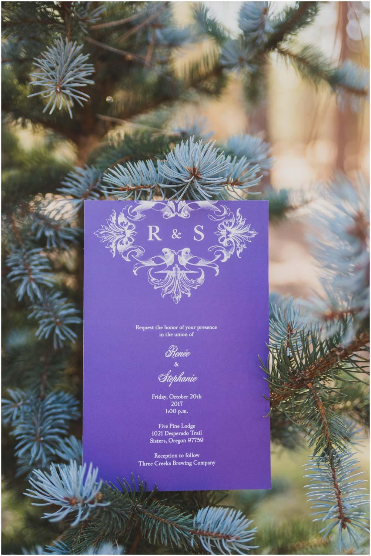 simple purple wedding invitation sitting a pine tree
