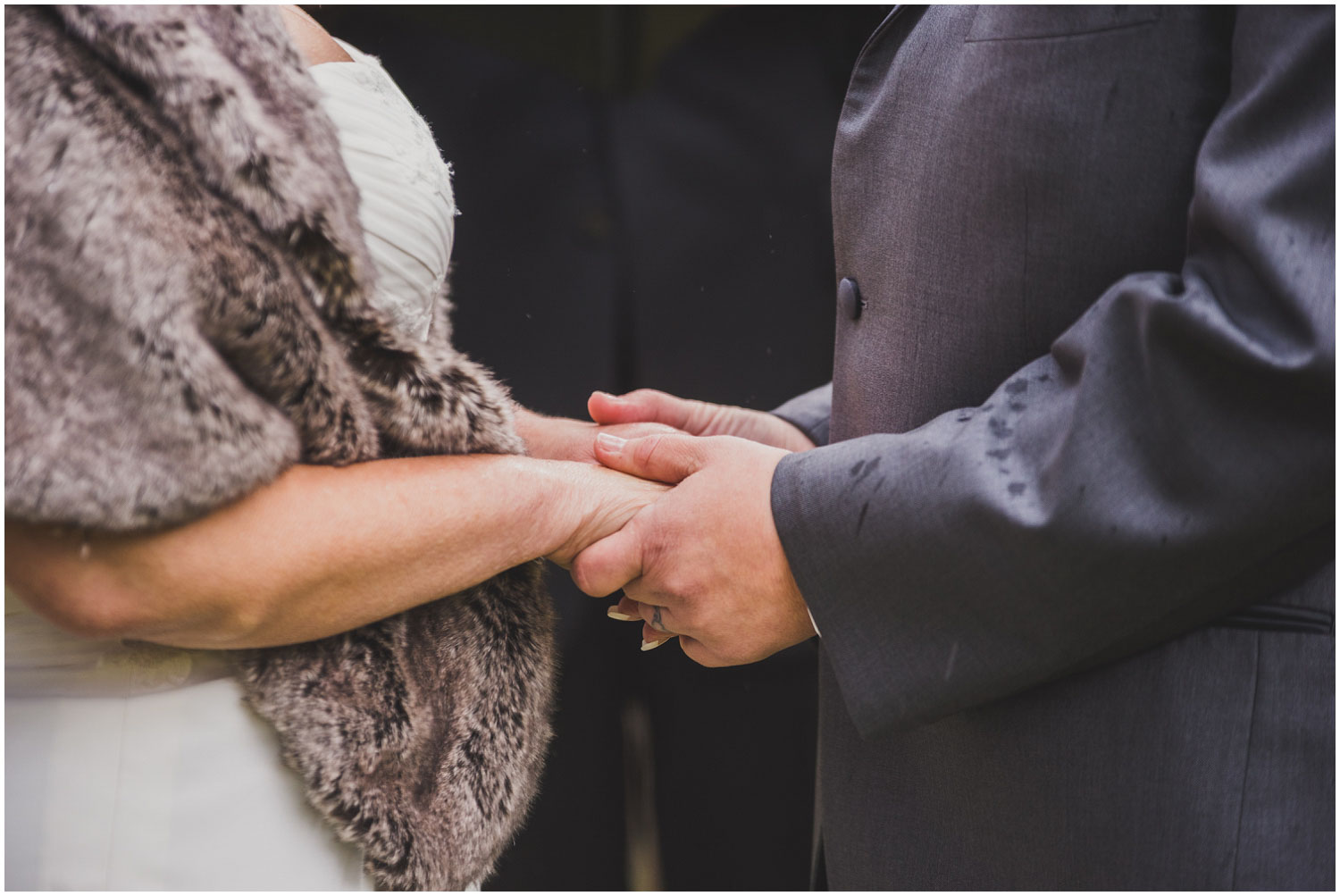 two brides holding hands during wedding ceremony