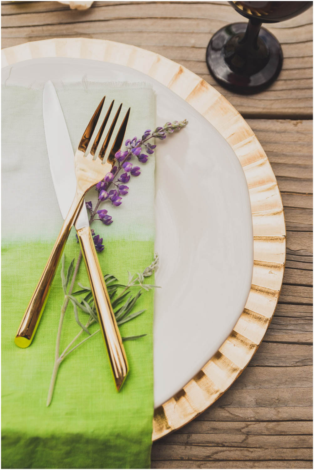 wedding sweetheart table place setting with gold flatware and wild lupine