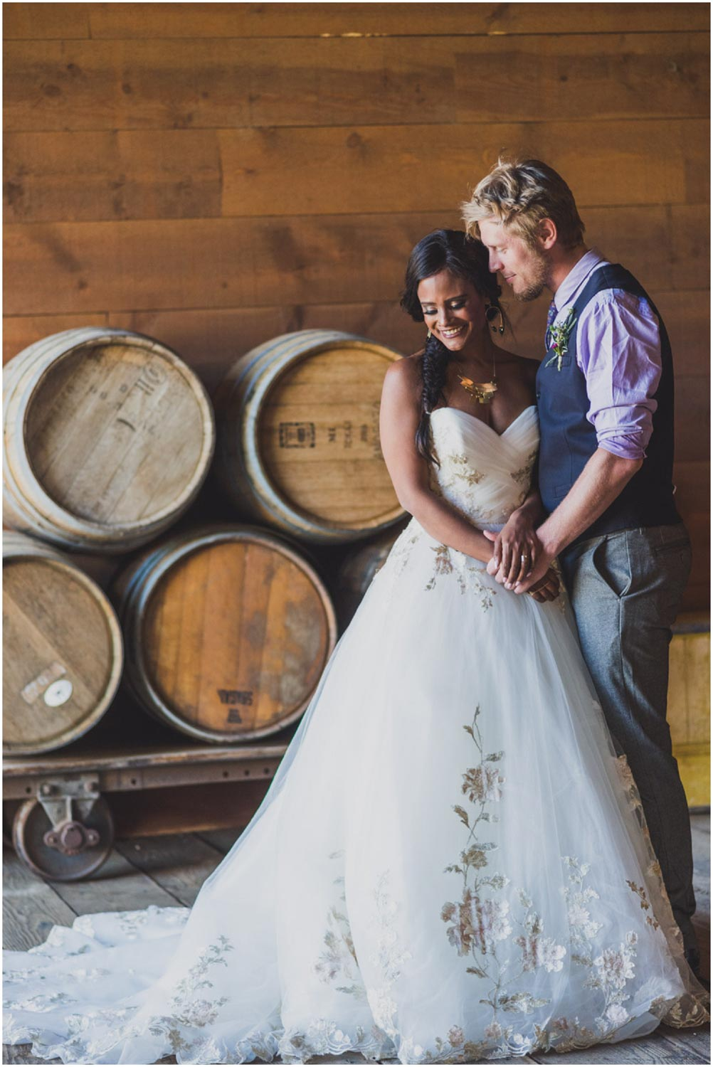 bride and groom snuggling next to wine barrels in tuscan stables ranch at the canyons terrebonne oregon